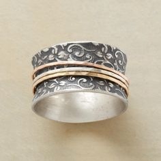 """ETERNALLY YOURS RING--An eternally yours spinner ring, with three slender rings—sterling silver, 14kt rose gold and 14kt yellow gold—spinning about an oxidized sterling silver band patterned with scrolling leaves. Whole sizes 5 to 9. 1/2""""W. This ring is licensed under U.S. Patent Nos. 6,497,117 and 6,395,732."""