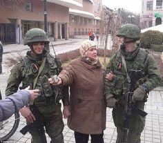 An elderly woman links arms with two Russian armed soldiers and asks for a photograph to be taking with them in the Crimean Peninsula