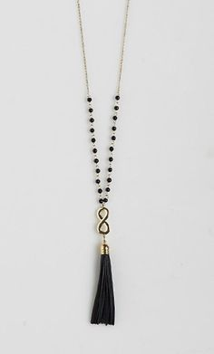 Long chain necklace with bead detailing and a faux leather tassel. Perfect for layering or worn...: