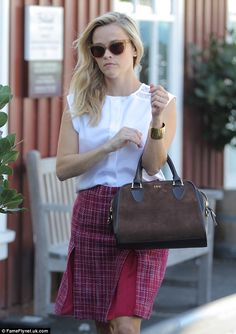 Fashionista: She also donned a pair of cat-eye sunglasses, and carried a stylish, brown le...