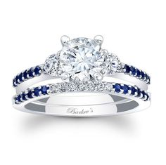 Classic elegance with clean lines, this three stone diamond engagement set, featuring an engagement ring with diamonds flanking the prong-set round diamond center.  The dainty shoulders are accented with shared prong set blue sapphires.  The wedding band shadows the engagement ring, set with diamonds and blue sapphires to match, adding the finishing touch of elegance to this unique set.