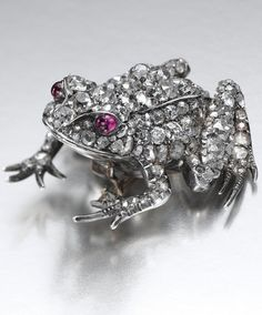 RUBY AND DIAMOND BROOCH, LATE 19TH CENTURY Designed as a sitting frog embellished with cushion-shaped, circular- and rose-cut diamonds to cabochon ruby eyes, one small diamond deficient, later pin fitting, accompanied by an associated detachable pin fitting.