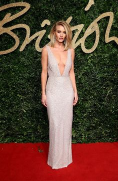 Rosie Huntington-Whiteley wears a gorgeous Burberry dress with a plunging neckline and chandelier earrings