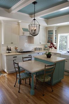 White cupboards, white subway tile back splash, coffered ceiling painted to match color of island, cage light, nice kitchen. Don't care for the chairs but the rest is pretty