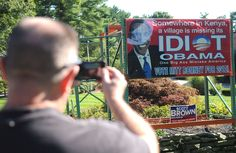 Retired Army Sgt. 1st Class Jim Smith, 49, of East Bridgewater, stops to take a picture of the anti-Obama signs on display in front of Sullivans, Inc., 121 Franklin St. in Hanson, seen on Sunday, August 26, 2012. (Emily J. Reynolds/The Enterprise) What do you think about that?