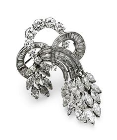 DIAMOND BROOCH, CIRCA 1950.  Designed as a triple loop supporting flexible cascades of foliate design, set with 21 marquise-shaped, 11 round and 72 baguette and tapered baguette diamonds weighing a total of approximately 14.75 carats, mounted in platinum.