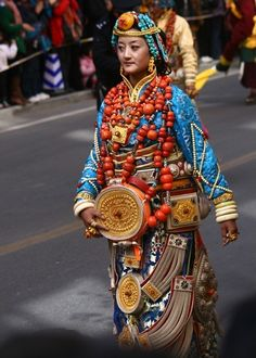 Government Celebrations in Kangding, Kardze, Tibet 2010 | A Khampa Tibetan woman in a traditional ceremonial costume from Palyul county. She wears the traditional women's headdress in Palyul with many strands of turqoise, and a gold necklace across her forehead. The costume and ornaments are probably the belongings of her family, and contain much of the family's wealth and savings.
