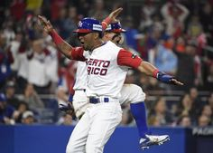 Eddie Rosario and Javier Baez of Puerto Rico celebrate after scoring during the sixth inning of their World Baseball Classic Pool F game against the US, at PETCO Park in San Diego, California, on March 17, 2017 (AFP Photo/Denis Porov)