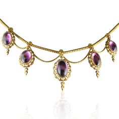 Victorian cabochon amethyst and gold fringe necklace, the gold snake pattern neckchain suspending five graduated oval amethyst and gold clusters each frame made up of a series of gold bead and trefoil motifs with black enamel detail and a similar tassle terminal, further gold festoons between, in fitted case by J. Turner