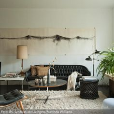 """Das Wohnzimmer bekommt durch die Vintage-Polstermöbel einen klassischen Look. Das """"Chromcraft""""-Sofa und der """"Scoop Chair"""" passen zu dem weichen Flokatiteppich ebenso gut wie zu dem außergewöhnlichen Wandbild von Monica Rezman."""