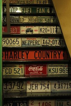 Basement Stairs Remodel: Stair treads are painted black & the risers are covered with license plates & some other signs. The stairs then become a kind of display case for the license plate collection.
