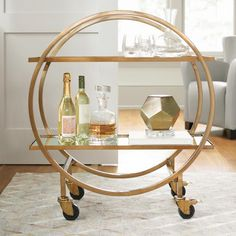To host your next party brilliantly with sparkling style, just invite adorable people and bring home the elegance and functional scope of the            Halsted Mobile Cart. A rolling bar or service cart with two roomy tray-style shelves to hold barware and bottles, it creatively designed to            work intelligently and give you real party staging flexibility. The modern, circular, open-design framework keeps your entertaining area from            feeling stuffy, dark, and fu...
