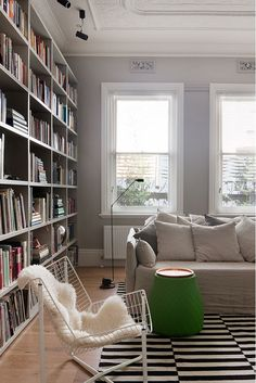 Small library in modern home with black and white carpet and sheepskin rug on white chair