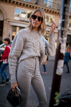 Paris Fashion Week street style includes high-waisted pants and bulky sweater, both in greige. Oh, and cool sunglasses.