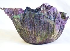 This purple mixed media bowl is made of handmade silk paper and has lime green accents. The silk paper is embedded with hand-dyed scrim, metallic Angelina fibers and miscellaneous threads. After constructing the silk paper, the bowl was sculpted, embellished with decorative stitching and hand beaded. This vessel is an irregular and unique organic shape. It is delicate and meant for decorative purposes only. I can construct mixed media vessels in other colors, sizes and shapes. Please…