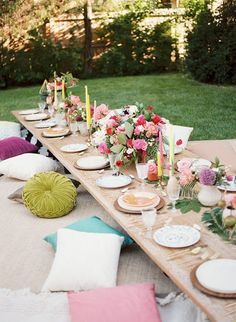 For this bohemian backyard bash, designer Jessie Capstick layered rugs and pillows to create comfortable floor seating, allowing for a more intimate and relaxed dinner.Via Inspired By This