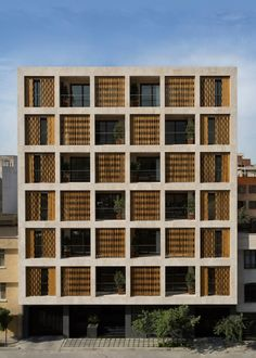 Wooden shutters can be drawn across the pigeonhole-style windows of this apartment block in Tehran