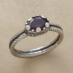 A single garnet, pillbox-set in sterling silver upon a sterling silver band. Lost-wax casting and then oxidation highlights its intricate design. Whole sizes 5 to 9.