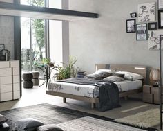 Tablet bed by Toma Italy. Functional bed in wood finish and contrast vertical headboard insert for added style. Elevated bed set on wooden peg style feet with arched headboard. Optional built in headboard lights for functional use and that delicate touch. Bed available in a range of wood finishes.