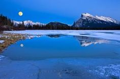 A clear winter night with a full moon rising up over the Fairholme Range and Mount Rundle sheds reflections on the surface of a partially frozen 2nd Vermilion Lake at twilight in Banff National Park, Alberta, Canada.