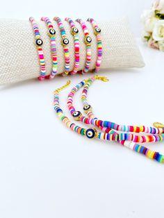 Evil Eye Bracelet, Rainbow Heishi Bracelet, Polymer Disc Bead, Beach Bracelet, Nazar Bracelet, Evil Eye Jewelry, Bohemian Jewelry, Greek Eye #evileye #plasticresin #lobsterclaw #bohohippie #evileyebracelet #nazarbracelet #heishibeads #beachbracelet #evileyejewelry #bohemianjewelry #rainbowbeads #polymerclaybeads Seed Bead Jewelry, Cute Jewelry, Beaded Jewelry, Evil Eye Jewelry, Evil Eye Bracelet, Beach Bracelets, Plastic Jewelry, Evil Eye Charm, Polymer Clay Beads