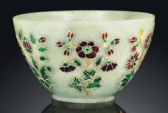 A MUGHAL-STYLE CELADON JADE BOWL  18TH/19TH CENTURY  The bowl is of deep rounded form supported by a short ring foot. The exterior is inset with enamels within gold and silver wires depicting lotus, prunus and chrysanthemum flowers with leafy stems. The stone is of an even dark celadon tone.