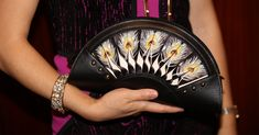 A model is holding a Bellorita black hand tooled and hand painted peacock feather leather crossbody clutch.