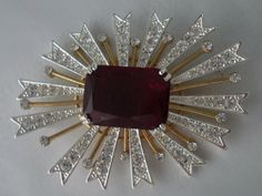 KJL Rhinestone Starburst Sunburst Vintage Brooch. Exclusive KJL silver and gold toned sunburst starburst brooch consisting of a large deep toned garnet rectangular prong set center stone with outlying clear rhinestone rays. The wider rays are silver toned accented with clear shiny circular rhinestones and the thinner rays are gold toned topped off with a clear circular rhinestone. Back clasp. Back earmarked KJL.