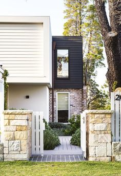 Sandstone pillars and a front gate painted in Dulux Grey Pebble Quarter welcome visitors. Scyon 'Linea' cladding is painted in Dulux Black Caviar, while recycled bricks from The Brick Pit add texture. | Photographer: Brigid Arnott