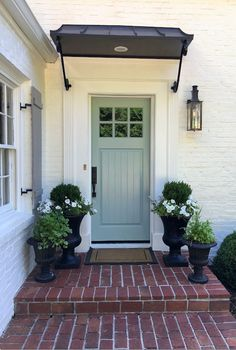 Benjamin Moore Wythe Blue front door on a beautiful white (SW Alabaster) brick home - built by Michael Ladisic. Cottage Front Doors, Green Front Doors, Front Door Porch, Front Porch Design, Exterior Front Doors, House Front Door, Front Entry, Front Door Planters, Porch Planter