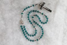 ☧ Catholic Prayer Beads / Religious Jewelry / Handcrafted rosary ☧  This is a beautiful handmade Faceted Crystal rosary with matte czech glass. This piece was handmade using a wooden crucifix with metal embellishments, and a beautiful madonna centerpiece. Great for both men and women.  *** ✞ ***  This rosary has faceted teal crystal beads (60 beads, 6mm) Measures: 5 Decades Total length is 17.5 Inches Crucifix is 2.25 inches tall  *** ✞ ***  Your item will be ready for shipping with...