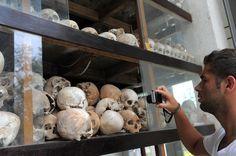 Um turista tira fotos de crânios das vítimas do Khmer Rouge exibidos no memorial do campo de extermínio Choeung Ek, em Phnom Penh, em 4 de maio de 2011. O regime comunista no Camboja matou quase um terço da população do país (Tang Chhin Sothy/AFP/Getty Images)