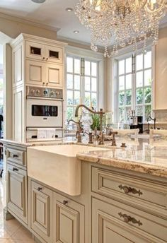 Chandelier in the kitchen farmhouse sink and white windows and cabinets .