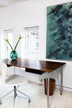 Arne Jacobsen har skabt skrivebordet med palisanderplade. Den hvide læderbetrukne Syver-stol er med originalt vip. Den grønne vase er fra Holmegaard, og Kjeld Hansen har malet billedet i havfarver.