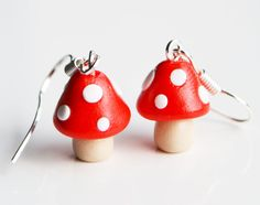 Miniature toadstool earrings handmade from fimo, polymer clay. The toadstools are red with white spots. The earrings are glazed to give a