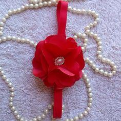 Flor de cetim vermelha na faixa de elástico.
