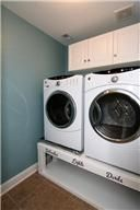 Laundry room with adorable custom, built-in space to house laundry baskets! #ForSale #LaundryRoom