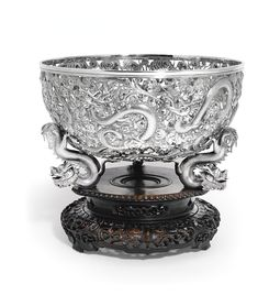 A Chinese export silver bowl, Wang Hing, Canton and Hong Kong, late 19th/early 20th Century circular, richly cast and chased with dragons and stylized clouds above three dragon supports, on carved hardwood stand