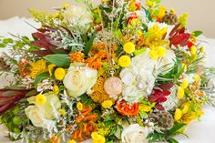A hand tied style bouquet made in a holder with trailing greenery and extensions.  Seasonal flowers in fall tones.  Dainty, spikey-type flowers and fillers.  This may include alstromeria, artemisia, gomphrena, heather, limonium, solidago, yarrow, scabiosa pods, mini coin flower, ivory roses, a hint of burgundy lecodendron or an accent of hydrangea, a mix of nice foliageand a simple ribbon to ¾ wrap and tie the exposed stems.