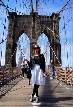 On the Brooklyn Bridge wearing a Club Monaco skirt, H&M leather jacket, Nike Roshe Run sneakers and Céline sunglasses