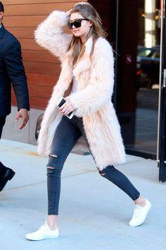 Look street style Gigi Haddid com tênis branco, jeans e maxi casaco de pele blush