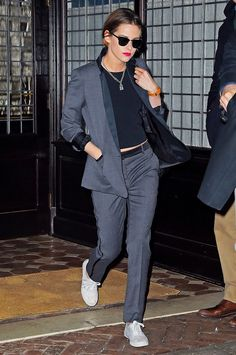 Kristen Stewart in a sleek gray suit, sneakers, and bold red lip