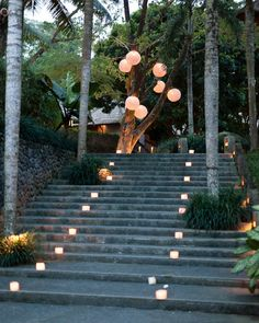For a destination wedding at the Alila Ubud resort in Indonesia, white lanterns were hung in bundles against tree trunks that seemed to mimic the look of tropical fruit.
