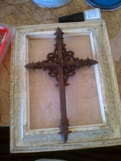 White washed old gold picture frame, burlap sack, and a rusty cross all held together with super glue.