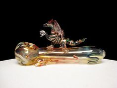This earth dragon on a pipe is all genuine hand blown glass made with a combination of art and science thick wall glass tubing. It is 3 inches tall, 5 1/2 inches long and 2 inches wide. The earth dragon can be fumed with a combination of colors or pastel colors.