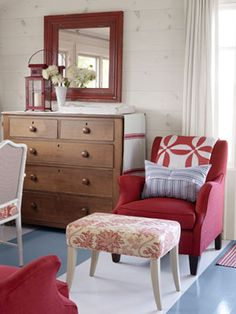 Red furniture and accessories accent a blue-and-white striped floor.