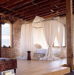 My dream bedroom. Exposed brick wall and king sized canopy bed.