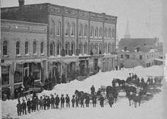 "Great Snow Storm of 1881    This stereoscopic of the east side of the Woodstock Square shows the square following the March 19, 1881 blizzard. Stone's Drug Store is on the far left. The ""Murphy Block"" is next, then across Jackson is the ""Rathole"" and a glimpse of the spire of the Lutheran Church on Jefferson Street.    The winter of 1881 was one of the worst on record in the 1800s, and was the subject of Laura Ingalls Wilder's The Long Winter."
