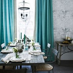 White and turquoise rustic dining room Wooden furniture has been combined with bold turquoise curtains in this striking scheme. The grey-toned map wallpaper ties the two contrasting colours together.