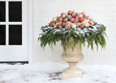 Martha Stewart shows you how to decorate a planter for the holidays with a pre-made wreath, live greenery and beautiful frosted ornaments.